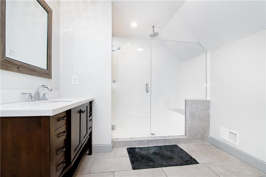 This full bath features a wonderful tiled shower with bench seat.